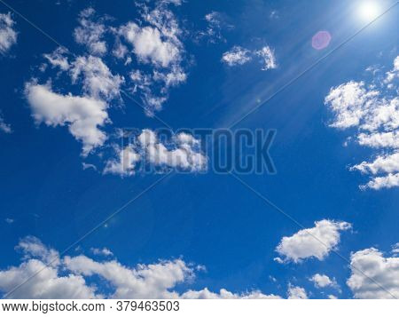 Sun On A Background Of Blue Sky With Clouds. Sun Rays With Glare. Space. Stratosphere. The Ozone Lay