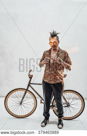 Tattooed Gangster Freak In Hawaiian Shirt And Sports Pants Standing Next To A Custom Made Bicycle. S
