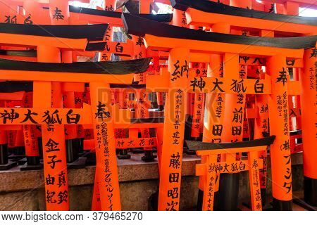 Kyoto, Japan, 08/11/19. Many Small Red Torii Gates With Prayers Left By Worshippers Along The Trail