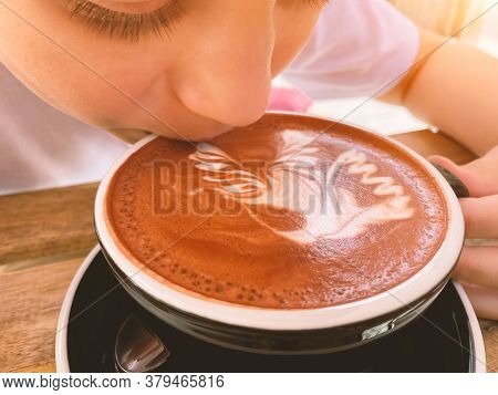 Close Up Of Young Teenage Boy Drinking Cocoa Drink Or Hot Chocolate With Latte Art At Home - Traditi