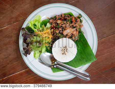 Thai Food Rice Topped With Stir Fried Pork And Basil Served With Vegetables On Wooden Table. Top Vie