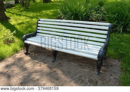 Modern White Wooden Bench On Black Wrought Iron Legs In A Shady Garden In Summer.