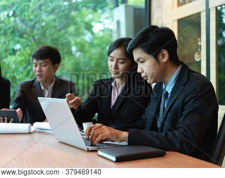 Portrait Of Office Workers Brainstorming On Their Project In Meeting Room