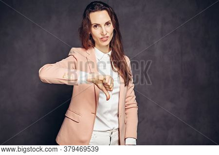 Adult Caucasian Woman Show Thumb Down On Grey Dark Background With Copy Space