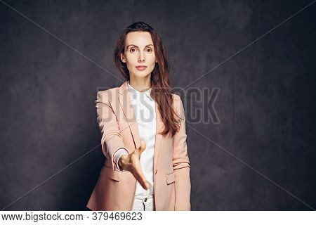 Adult Caucasian Woman Shaking Hand On Grey Dark Background With Copy Space
