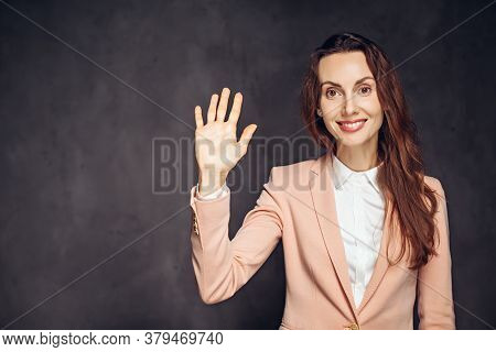 Adult Caucasian Woman Show Hello Gesture On Grey Dark Background With Copy Space