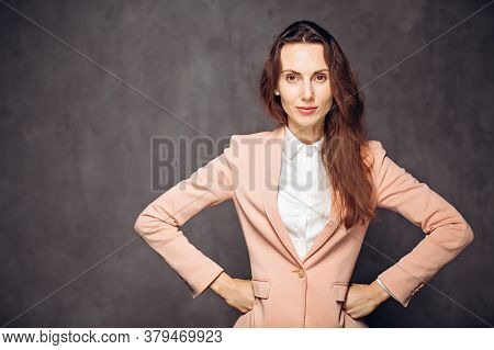 Adult Caucasian Woman With Hands On Hips On Grey Dark Background With Copy Space