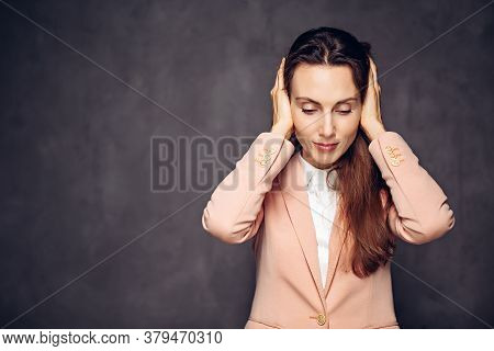 Adult Caucasian Woman Covering Ears On Grey Dark Background With Copy Space