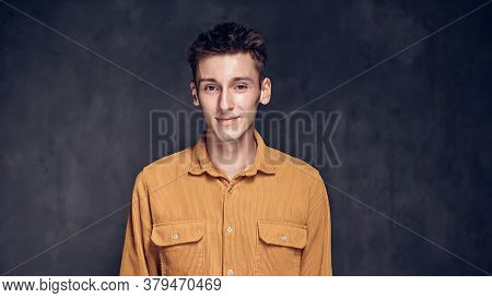 Smiling Young Caucasian Man On Grey Dark Background With Copy Space