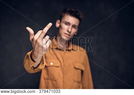 Young Caucasian Man Show Middle Finger On Grey Dark Background With Copy Space