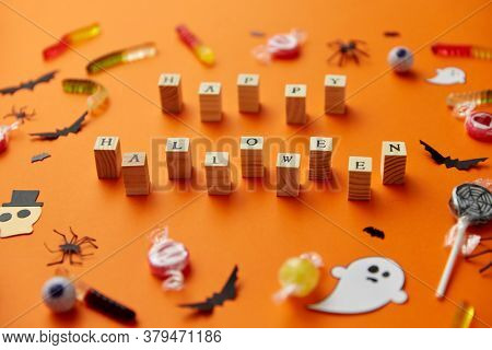 halloween and holiday concept - wooden toy blocks with trick or treat lettering candies and decorations on orange background