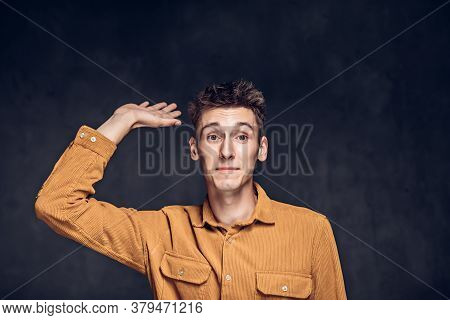 Young Caucasian Man Show Hello Gesture On Grey Dark Background With Copy Space