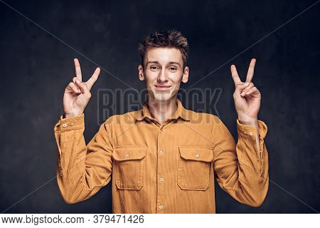 Young Caucasian Man Show Victory Sign On Grey Dark Background With Copy Space