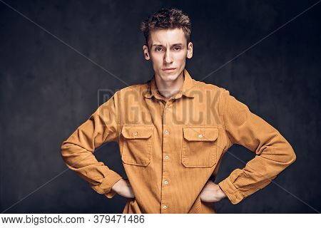 Young Caucasian Man With Hands On Hips On Grey Dark Background With Copy Space