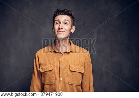 Worried Young Caucasian Man On Grey Dark Background With Copy Space
