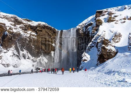 Skogafoss,iceland - March 5, 2020: Tourists At Skogafoss Waterfall, One Of The Biggest Waterfalls An