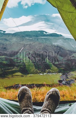 Legs In Knitted Gray Woolen Socks. Morning View From The Tent On The Caucasus Mountains To Elbrus. T
