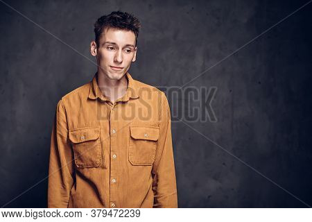 Upset Young Caucasian Man On Grey Dark Background With Copy Space