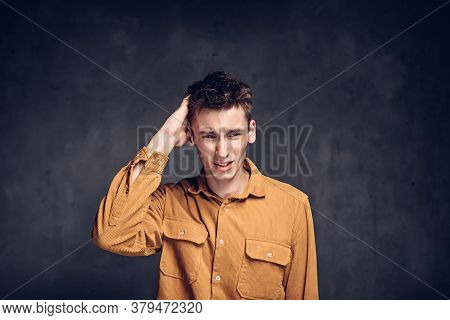 Young Caucasian Man With Migraine On Grey Dark Background With Copy Space