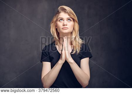 Young Caucasian Woman Pray On Dark Background