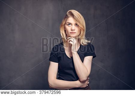 Pensive Young Caucasian Woman On Dark Background