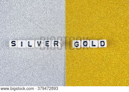 Silver  And Gold Words Formed By White Dices With Black Letters  Laying On Silver And Golden Backgro