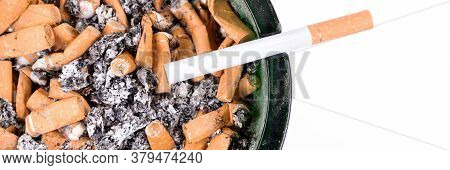 Many Cigarette Butts In The Glass Ashtray. Panoramic Image