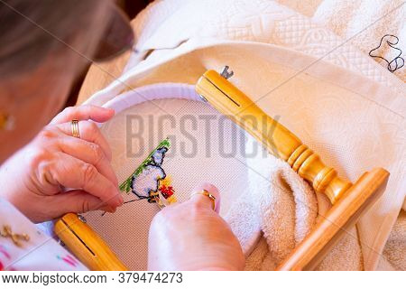 A Woman Cuts The Thread At The Back Of A Cross Stitch Pattern. Concepts Of Manual Work Or Work At Ho