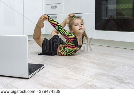 Baby Does Gymnastics At Home Online. Does Exercises In Front Of A Laptop