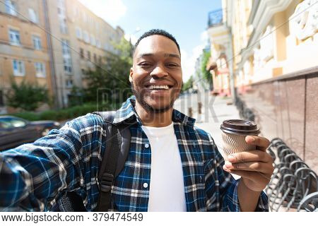 Time For Coffee And Selfie. Smiling African Guy Taking Selfportrait On Camera, Holding Takeaway Coff
