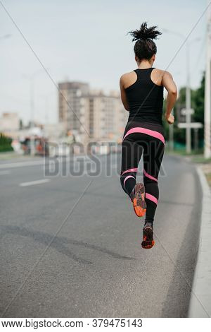 Morning Jog On Road In City. Muscular African American Girl In Sportswear Froze In Air, Jogging Outd