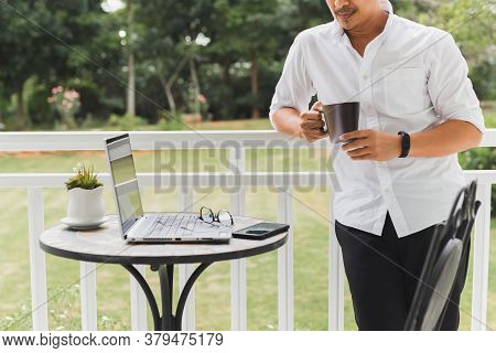 Businessman Relax Standing On Terrace Hand Holding Coffee With Laptop On Table