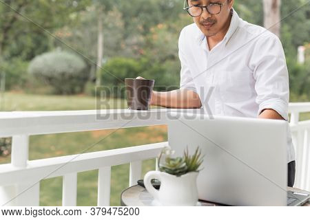 Businessman In Glasses Holding Coffee While Working On Laptop