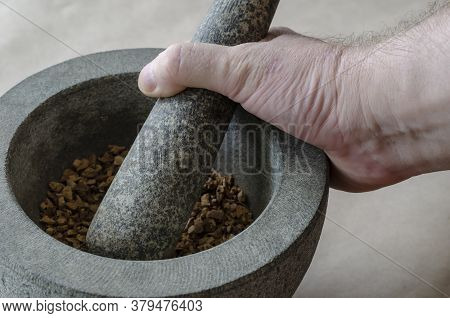 The Hand Of An Adult Caucasian Man Grinds Random Medicinal Roots And Herbs In Stone Mortar.