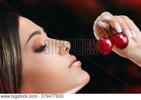 Extreme Close Up Side View Portrait Of Sensual Woman. Hand With Long Nails Holding Red Cherries Next