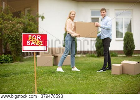 Sold Sign And Young Couple Carrying Cardboard Box At House Yard, Selective Focus. Copy Space