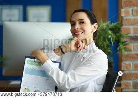 A Smiling Woman Is Sitting At The Workplace With A Statistical Report In Her Hands. The Employee Car