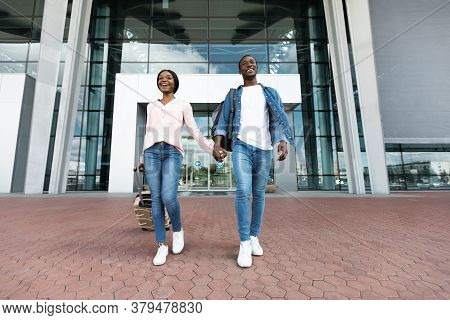 Ready For Adventures. Excited Black Couple Leaving Airport Building In New Country, Enjoying Travell