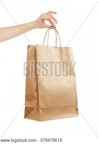 Female hand holding kraft paper shopping bag. Design mockup Isolated on white background.