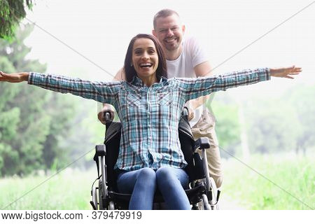 A Guy And A Woman In A Wheelchair Are Walking In The Summer Forest. A Disabled Woman Is Happy With A