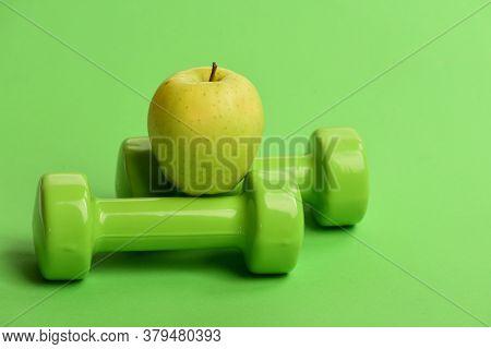 Diet And Sport Regime Concept. Apple Fruit Near Lightweight Barbells