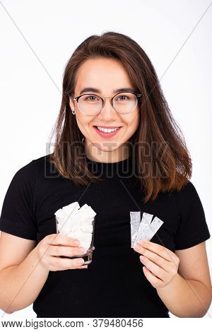 Young Beautiful Woman In Glasses With A Smile, Holds In One Hand A Glass Of White Sugar, In The Othe