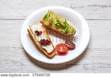Toasted Baguette With Avocado And Cheese. On A Light Wooden Background.