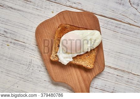 Toast With Poached Egg On A White Plate.