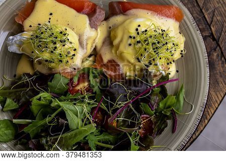 Eggs Benedict On English Muffin With Smoked Salmon, Lettuce Salad Mix, And Hollandaise Sauce.