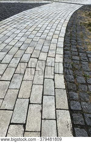 Pavement Is Lined With Old Stone. Gray Retro Stone Texture. Pedestrian Zone In The Park In Daylight.