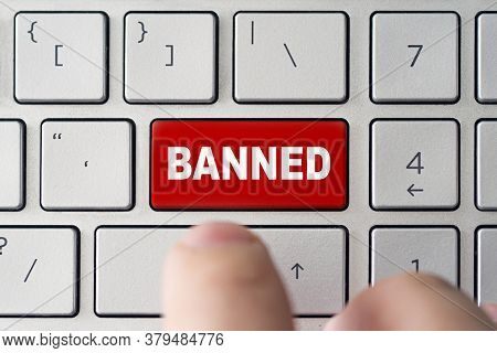Admin Bans The User. The Red Button On The Keyboard Of A Notebook With The Inscription Of Banned. Th