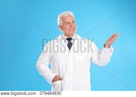 Happy Senior Man In Lab Coat On Light Blue Background