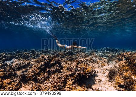 Woman Freediver Glides Underwater In Ocean. Freediving With Fins