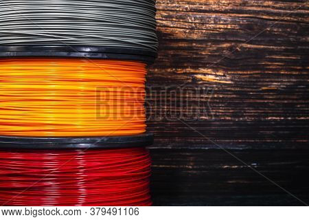 Three Coils Of Filament For 3d Printing. Bright Thermoplastic Of Orange, Red And Grey Colors.